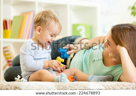kid and mom playing with toy animals indoors - stock photo
