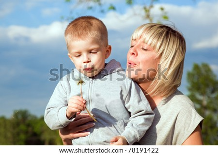 Kid and mother blowing dandelion. Spring time - stock photo
