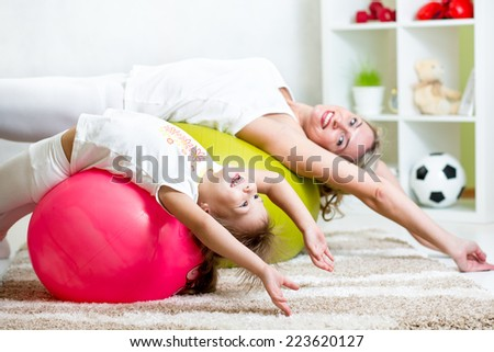 kid and mother doing gymnastic exercises with fitness ball at home - stock photo