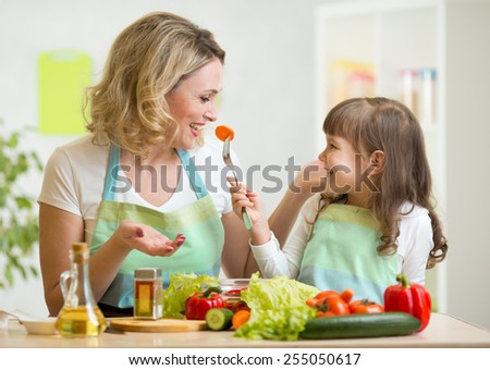 kid and mother eating healthy food vegetables - stock photo