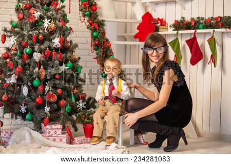 Kid and mother near new-year tree - stock photo