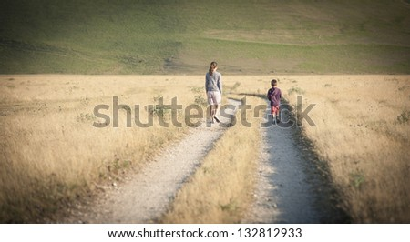 Kid and mother walking outdoors. Castelluccio di Norcia, Monti Sibillini Park, Italy. - stock photo