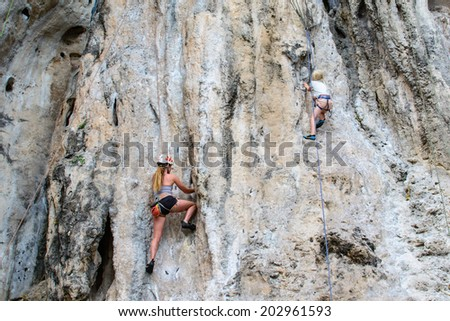 Kid and Woman climbing on the rock - stock photo