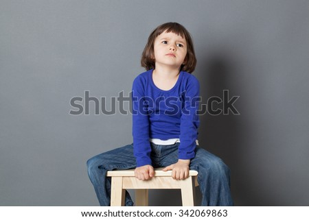 kid attitude concept - angry 4-year old child sulking on a stool for discipline or calming down in the corner for bad behavior,studio shot - stock photo