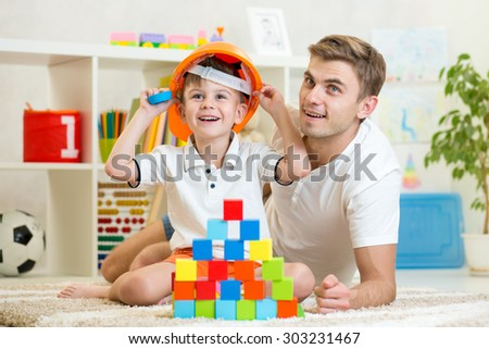 kid boy and father play builders in children room - stock photo