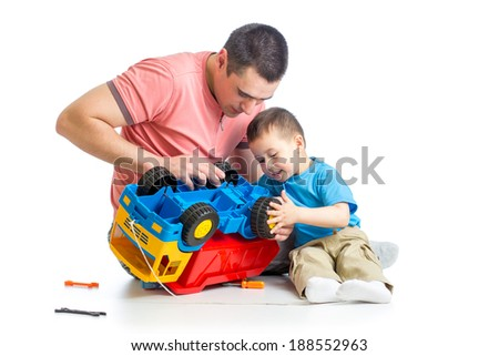 kid boy and his dad repair toy trunk - stock photo
