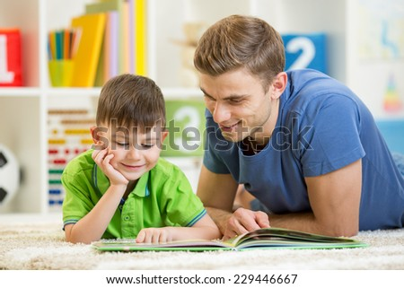 kid boy and his father reading a book on floor indoors - stock photo