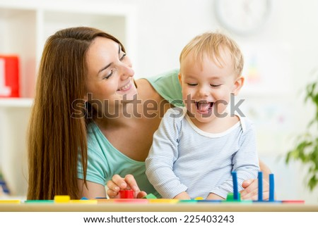 kid boy and mother playing at table at home - stock photo