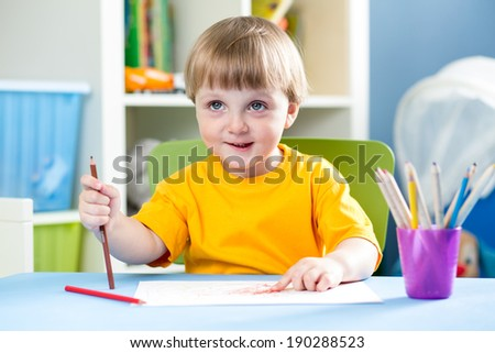 kid boy drawing with pencils indoors - stock photo