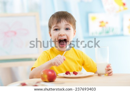 kid boy eating healthy food at home - stock photo