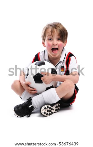 Kid / Boy in complete german soccer outfit sitting on the floor and stick out his tongue - stock photo