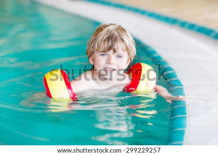 Kid boy of 4 years with swimmies learning to swim in an indoor pool. Active and fit leisure for children. - stock photo