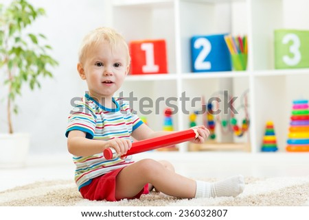 kid boy sitting with big red pencil indoor - stock photo