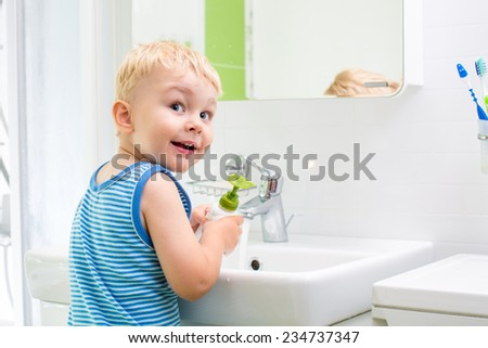 kid boy washing his face and hands with soap in bathroom - stock photo