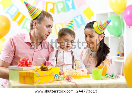 kid boy with parents blow candle on birthday cake - stock photo