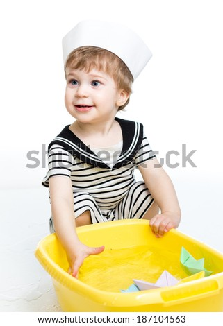 Kid boy with sailor hat  playing with paper boats - stock photo