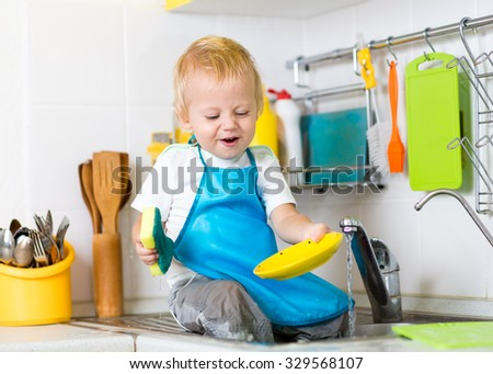 Kid child boy washing dishes and having fun in the kitchen - stock photo
