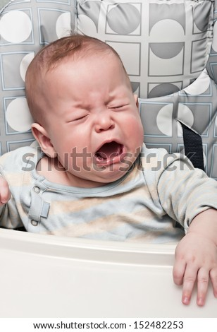 kid cries sitting in a chair for feeding - stock photo