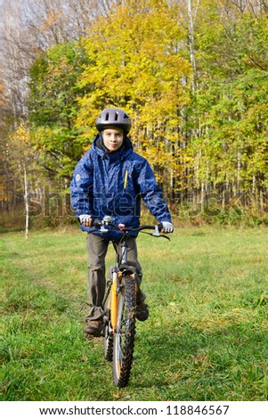 Kid cycling in autumn park - stock photo