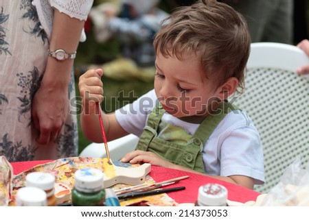 Kid decorating wooden horse toy at the workshop - stock photo