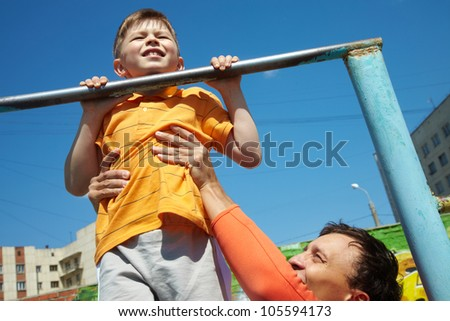 Kid doing chin-ups, his father helping him - stock photo