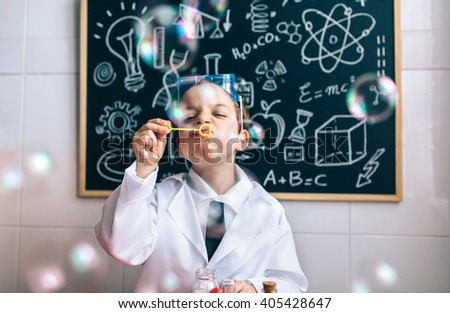 Kid doing soap bubbles against of drawn blackboard - stock photo