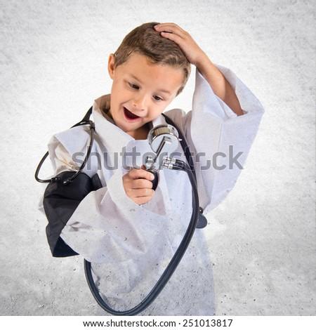Kid dressed like doctor doing surprise gesture - stock photo