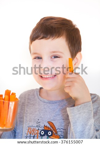 Kid eating delicious carrot - stock photo