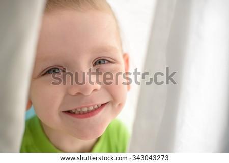kid face smiling under blanket - stock photo