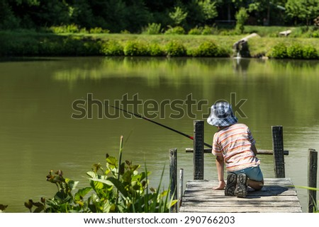 Kid fishing on the lake - stock photo