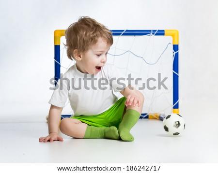 kid football player looking at soccer ball - stock photo