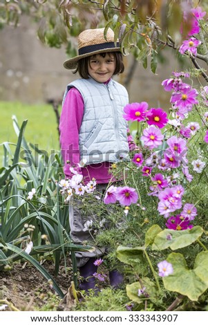 kid gardening concept - smiling preschool child enjoying posing in purple flowers with straw hat on in home vegetable garden in autumn season, outdoors view - stock photo