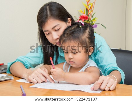 kid girl and her mom reading and writing a book together - stock photo
