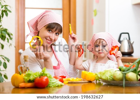 kid girl and her mother cooking in kitchen at home - stock photo