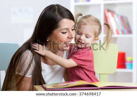 kid girl and mother read a book together indoors - stock photo
