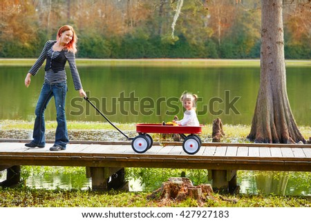 Kid girl and mother walking in the park lake with pull cart - stock photo