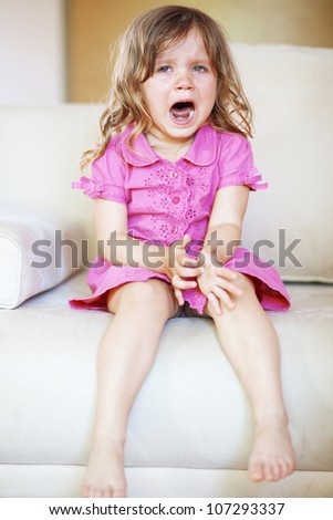 Kid girl cries sitting on the sofa - stock photo