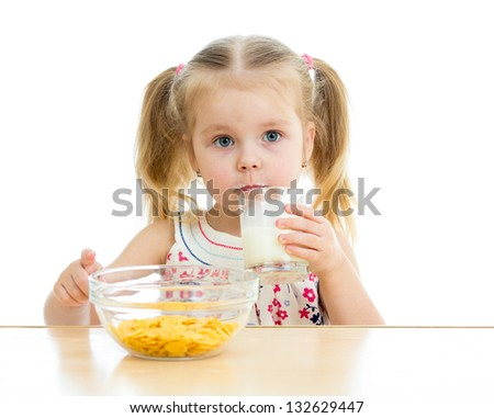 kid girl eating corn flakes with milk over white - stock photo
