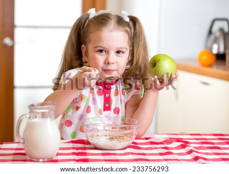 kid girl eating healthy food in kitchen - stock photo