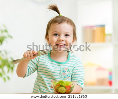 kid girl eating healthy vegetables food at kitchen - stock photo