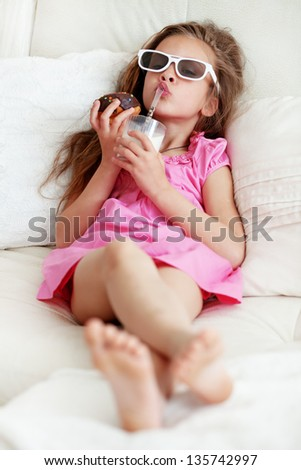 Kid girl eating sweet donuts and drinking milk lying on a sofa - stock photo