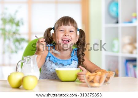 kid girl eats healthy food at home or kindergarten - stock photo