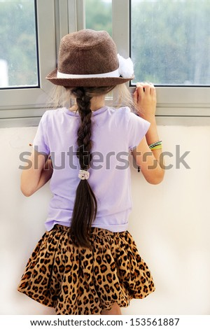 Kid girl in the hat with long brunette braid looking through the window  - stock photo