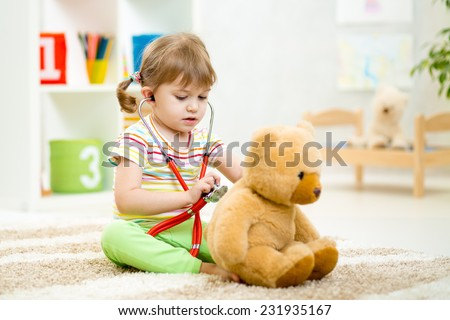 kid girl playing doctor with plush toy at nursery - stock photo
