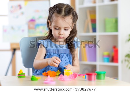 Kid girl playing with plasticine at home - stock photo