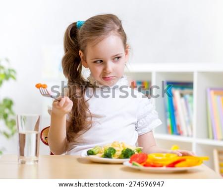 kid girl refuses to eat healthy food - stock photo