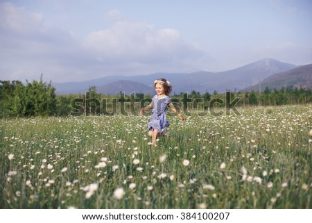 Kid girl running through a field with daisies - stock photo