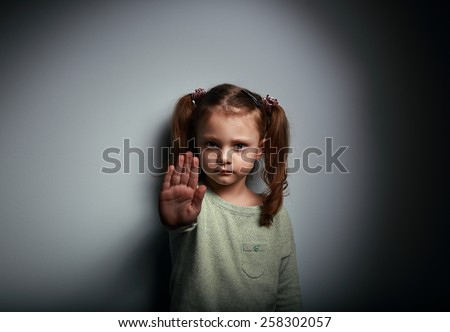 Kid girl showing hand signaling to stop useful to campaign against violence and pain on dark background with empty copy space - stock photo