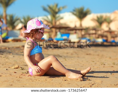 Kid girl sitting on the beach sand and sunbathing - stock photo