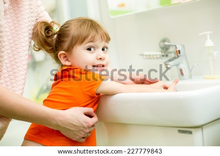 kid girl washing hands with mom help in bathroom - stock photo